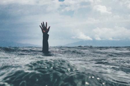 Eine Hand ragt hilfesuchend aus den Wellen im Ozean hervor. Versunken im Alltag.
