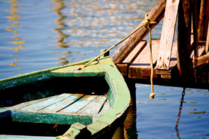 Achtsamkeit an der Mecklenburgische Seenplatte: ein grünes Holzboot ist ein einem Balken festgebunden.