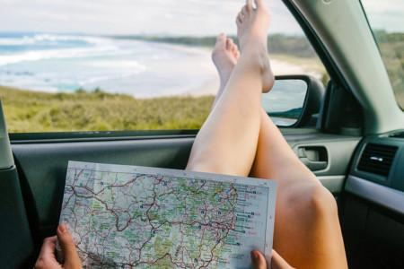 Entspanntes Deutschland: eine Frau hängt ihre Beine zum offenen Autofenster raus. Sie blickt auf das Meer, auf ihrem Schoß liegt eine Landkarte.
