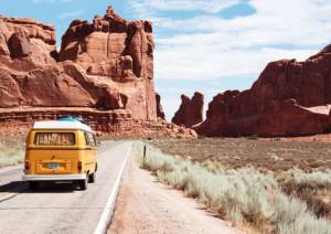 Urlaub mal anders: im VW-Bus reisen bedeutet Freiheit pur. Ein gelber alter Bulli fährt durch eine felsige Wüstenlandschaft.