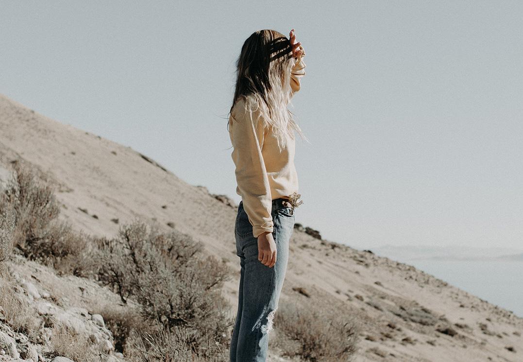 Was ist Achtsamkeit? Eine Frau steht an einem Hang und schaut in die Ferne, sie genießt das Hier und Jetzt
