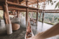 Retreat-Urlaub: Eine Person entspannt in einer Hängematte, die in einem offenen Holzhaus mit Blick auf den Dschungel hängt.