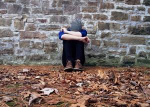 Mental Health: Person sitzt einsam vor einer Mauer, den Kopf in die Arme versenkt