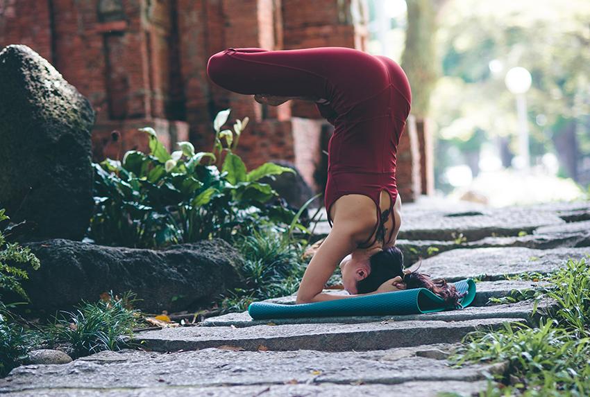 8 Yoga Irrtümer: eine Frau macht Kopfstand auf ihrer Yogamatte im Freien. Die Beine sind dabei verschränkt.