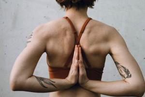 8 häufige Yoga Irrtümer: eine Frau legt ihre Handflächen hinter dem Rücken aneinander und praktiziert die Reverse Prayer Pose