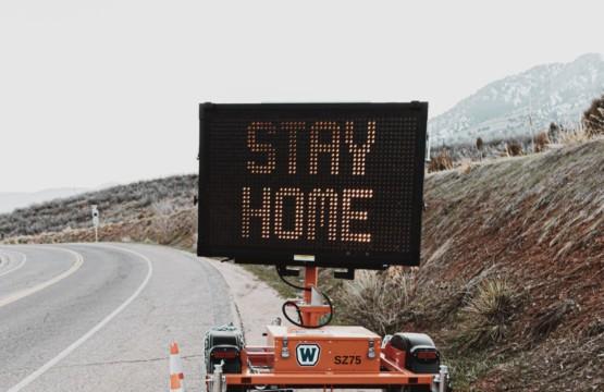 """Achtsam durch die Krise: an einer leeren Straße steht ein mobiles Schild mit der Aufschrift """"Stay home"""""""