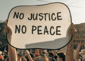 """Lektionen der Corona-Krise. Bei einer Demonstration hält eine Person ein Schild hoch mit der Aufschrift """"No justice - no peace""""."""