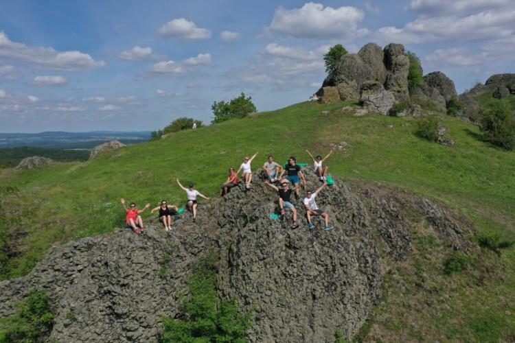 TreeYourMind | Während der achtsamen Wanderung im Habichtswald entspannt die Gruppe auf einem Felsen
