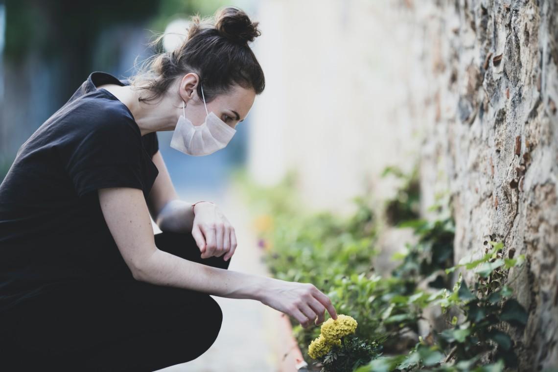 Eine Frau trägt eine Maske und erfreut sich an einer kleinen Blume am Straßenrand.