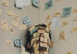 Ein Mann ist komplett mit Post-it Zetteln vollgeklebt, die signalisieren, wie viel Arbeit er noch zu erledigen hat.