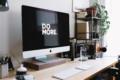 An einem Arbeitsplatz steht ein Monitor dessen Bildschirmschoner sagt: Do More.