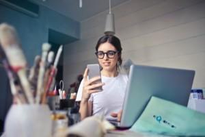 Eine Frau sitzt glücklich an ihrem Schreibtisch und widmet sich der Arbeit.