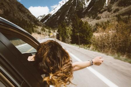 Eine Frau auf dem Weg zu einem Retreat in Deutschland lehnt sich während der Fahrt aus dem Autofenster
