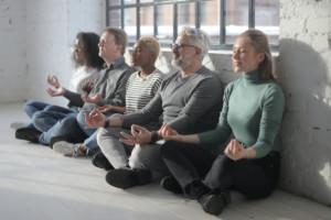 Business Meditation: Ein paar Arbeitskollegen sitzen in einer Reihe und meditieren gemeinsam