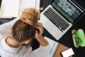 Stress am Arbeitsplatz. Eine Frau beugt sich gestresst über ihren Computer.