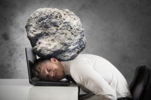 Stress im Büro. Ein Mann hat den Kopf auf den Laptop gelegt, auf ihm lastet ein riesiger Stein.