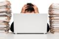 Stress im Büro. Ein Mann versinkt zwischen Aktenstapeln und Computer
