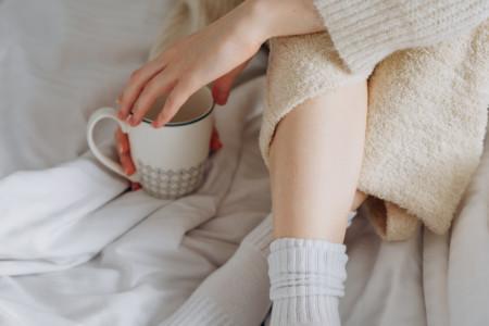 Eine Frau trinkt einen Kaffee im Bett – so kann auch eine gesunde Morgenroutine aussehen.