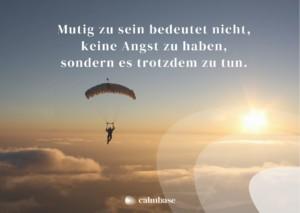 Ein Fallschirmspringer fliegt in den Sonnenuntergang. Auf dem Bild steht ein Zitat: Mutig zu sein bedeutet nicht, keine Angst zu haben, sondern es trotzdem zu tun.