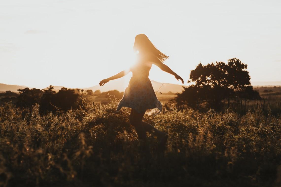 Eine Frau tanzt im Sonnenuntergang